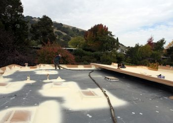 Armstrong roofing system - a technician sprays spf on a flat roof