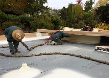 Armstrong Roofing - two men on a flat roof installing spf roofing