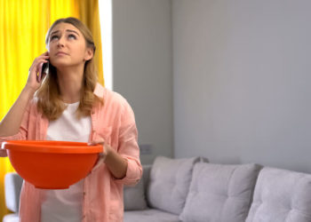 Woman holding a bowl to catch water from flat roof leaks